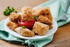 Pepitas de pollo en la placa blanca con la salsa de tomate Imagen de archivo