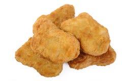 Pepitas de pollo frito en el fondo blanco Foto de archivo libre de regalías