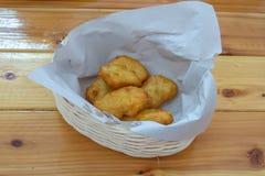 Pepitas de pollo frito en una cesta en una tabla de madera imagenes de archivo