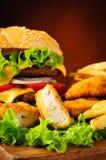Pepitas de pollo, hamburguesa y patatas fritas Imagenes de archivo