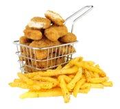 Pepitas e batatas fritas de galinha em um fio pequeno que frita a cesta fotografia de stock