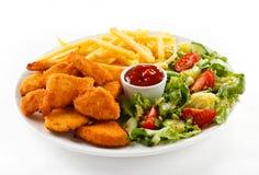 Pepitas e vegetais de galinha fritada imagem de stock royalty free