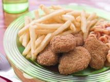 Pepite di pollo con i cerchi ed i chip degli spaghetti Immagini Stock