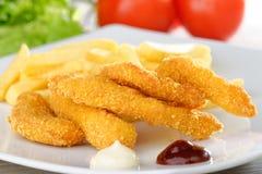 Pepite di pollo/dita appiccicose con le patate fritte Immagini Stock