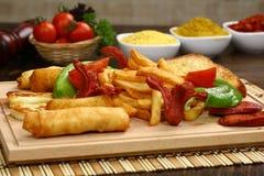Pepite di pollo miste, patate fritte e salsiccie Fotografie Stock