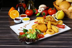 Pepite di pollo miste, patate fritte e salsiccie Immagini Stock