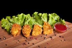 Pepite di pollo, su una tavola di legno con salsa e lattuga Fotografie Stock Libere da Diritti