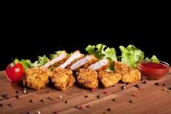 Pepite di pollo, su una tavola di legno con salsa e lattuga Fotografia Stock