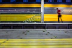 Pepople在与快速地移动行动迷离的火车的火车站中 库存照片