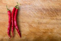 peppar för röd chili över trä Royaltyfri Bild