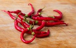 Peppar för röd chili över trä Arkivbilder