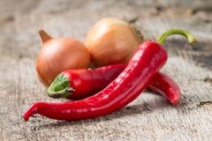 Peppar för röd chili med löken på bakgrund. Selektiv fokus Arkivbild