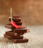 Peppar för röd chili på bunten av mörka chokladstycken Arkivfoto