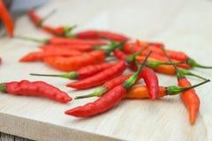 Peppar för röd chili på trä som hugger av bakgrund Arkivfoton