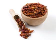 Peppar f?r chilipeperoncinipaprika i tr?bunke och skopan som isoleras p? vit bakgrund Kryddor och matingredienser royaltyfri bild