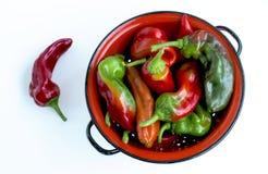 Peppar i en röd durkslag från över Arkivfoto