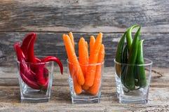 Peppar och morötter för Ð-¡ hili i exponeringsglas på träbckgroung Royaltyfria Bilder