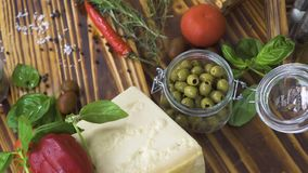 Peppar, oliv, tomater, ost, lökar, vitlök och kryddor för att laga mat på köksbordet Slut upp nya ingredienser stock video