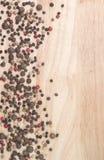 Peppar på bakgrunden av träbräden Arkivfoton