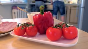 Peppar, tomater och skinka på köksbordet Familjen lagar mat matställen hemma arkivfilmer