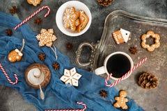 Pepparkaka, godisrotting och kaffekopp på den mörka tabellen för julsammansättning för bauble blått exponeringsglas fotografering för bildbyråer