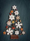 Pepparkaka muttrar, kryddor, torkad apelsinskal att skapa en julgran på en mörkerstenbakgrund royaltyfri bild