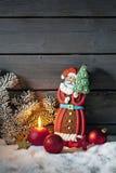 Pepparkaka Santa Claus på högen av snö mot träväggen royaltyfria foton
