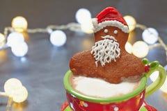 Pepparkakajultomten i en varm kopp av cappuccino Arkivfoto