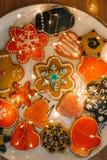 Pepparkakakakor på den vita maträtten med guld- ljus arkivfoton