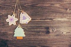 Pepparkakakakor som hänger över träbakgrund kopiera avstånd arkivfoto