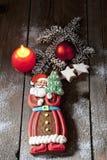 Pepparkakan Santa Claus med kanelbruna stjärnor för stearinljuset sörjer fattar julkulan på trägolv Royaltyfri Foto