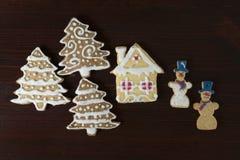 Pepparkakasnögubbe, julträd och hus på en träbaksida arkivbild