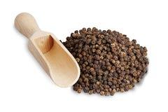 Pepparkorn och en sked av ljust trä för kryddor Royaltyfri Bild
