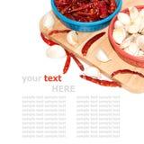 Peppe y ajo rojos en tabla de cortar Fotos de archivo libres de regalías