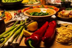 Pepper and asparagus. Pepper and aspargus on kitchen dinner table filled with pizza, pasta and vegetables stock photos