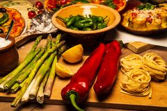 Pepper and asparagus. Pepper and aspargus on kitchen dinner table filled with pizza, pasta and vegetables royalty free stock images