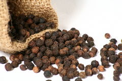 Pepper Bag. Black pepper spilling out of a small hessian bag Royalty Free Stock Photo