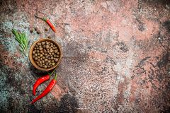 Pepper in bowl with red pepper in the pod. On rustic background stock image