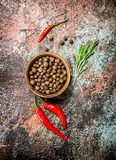 Pepper in bowl with red pepper in the pod. On rustic background stock photography