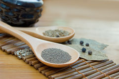 Pepper, cumin and bay leaf. On wooden plate Royalty Free Stock Image