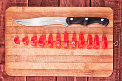 Pepper cut to slices, kitchen knife and cutting board Royalty Free Stock Photos