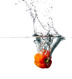 Pepper drops into a water Stock Images
