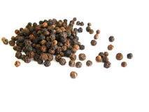 Pepper grains. Black pepper grains over white Royalty Free Stock Images