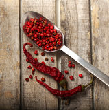 Pepper and grains on wooden background. Pepper and grains in spoon on wooden background Stock Photo