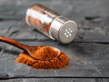 A pepper jar and a spoon of ground chili on a rustic table. Universal seasoning for all dishes royalty free stock photos