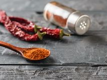 A pepper jar, three pods and a spoon of ground chili on a rustic table. Universal seasoning for all dishes royalty free stock photos