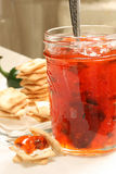 Pepper Jelly. Jar of pepper jelly with serving spoon and crackers stock photos
