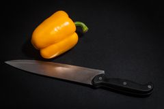 Pepper with a knife. Still life of a yellow pepper with a knife Royalty Free Stock Image