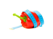 Pepper and a measuring tape on white background. Red pepper and a measuring tape on white background close-up Royalty Free Stock Photo