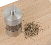 Pepper mill. On cutting board with salt Royalty Free Stock Images
